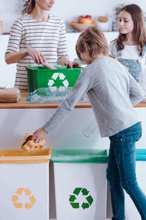 Famiglia che ordina i rifiuti in pattumiere a casa
