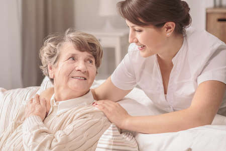 Helpful, young, pretty nurse supporting a lovely older lady with alzheimer in a retirement home Zdjęcie Seryjne