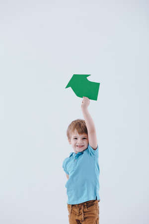Young, cheerful boy holding a green recycling symbol on white background Stockfoto