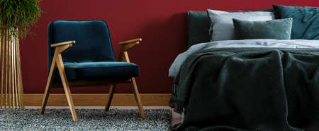 Blue wooden armchair next to green bed in colorful bedroom interior with red wall and plant