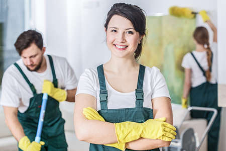Smiling cleaning lady in a green uniform and yellow rubber gloves at work