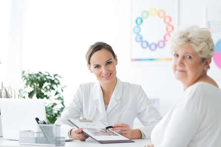 Young dietician sitting by the desk in her office with a senior patient and looking directly at the camera
