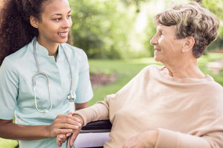 Senior woman and her doctor spending time in the garden outside of the hospital Stock Photo
