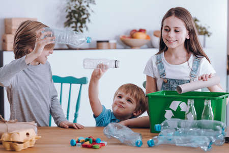Siblings having fun while segregating waste at home Standard-Bild