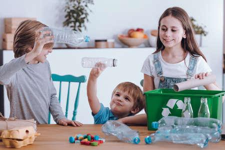 Siblings having fun while segregating waste at home Stockfoto