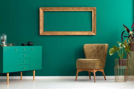 Armoire verte et fauteuil à côté de la plante dans le salon intérieur avec maquette sur le mur Banque d'images - 99219149