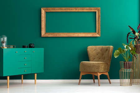 Green cupboard and armchair next to plant in living room interior with mockup on the wall
