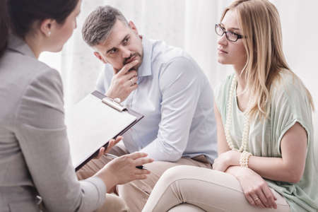 Upset young woman talking to a female psychologist, with her husband by her side during marital counseling