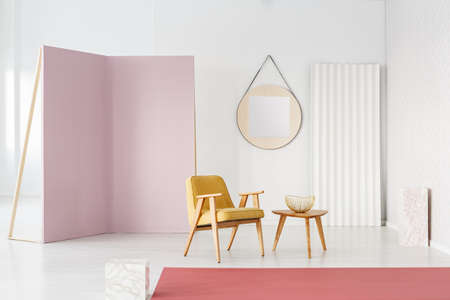 Pastel photo studio interior with yellow armchair, movable, purple wall and round mirror
