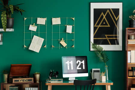 Black and gold poster with geometric pattern hanging on the wall in green interior with retro gramophone and computer