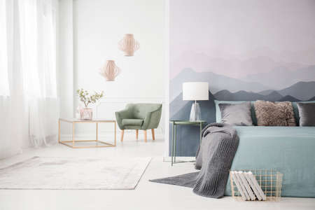 Lamp on table next to bed with grey bedding in open space interior with green armchair Stock Photo