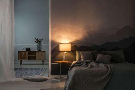 Interior del dormitorio por la noche con luz cálida de la lámpara en una mesita de noche cerca de un armario de madera Foto de archivo