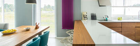 White countertop and violet heater in modern kitchen interior with wooden dining table