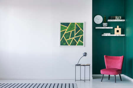 Red chair next to table with lamp against white wall with green painting in living room interior