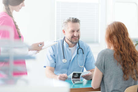 Optimistic doctor explaining ultrasound image to his patient and nurse taking notes Stock Photo