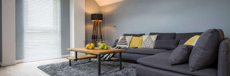 Lamp in the corner of cozy living room interior with wooden table and yellow pillow on sofa