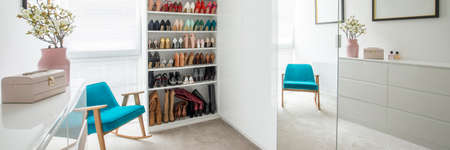 Flowers on white cabinet in pastel dressing room interior with blue armchair next to shelves with shoes Stock Photo