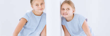 Close-up of a happy girl with her ear to the wall and her twin sister in the other room Standard-Bild