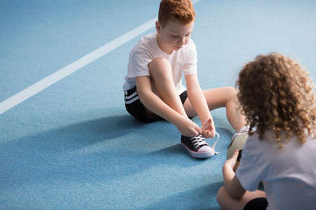 Young boy sitting on a blue floor and tying the shoelaces before physical education classes Stok Fotoğraf - 104830376