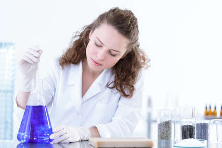 Chemist mixing a blue solution with the test substance during laboratory analysis
