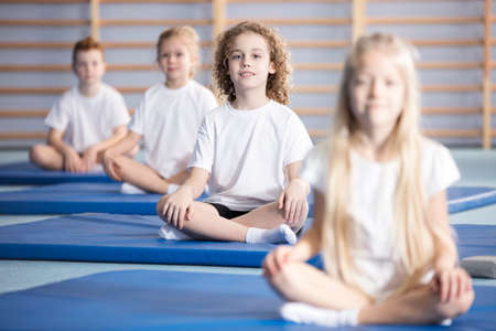 Smiling boy and friends sitting on blue mats during a corrective gymnastics class