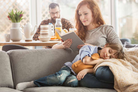 Sleeping son lying on mother's lap while she is reading a book and father eating in the background