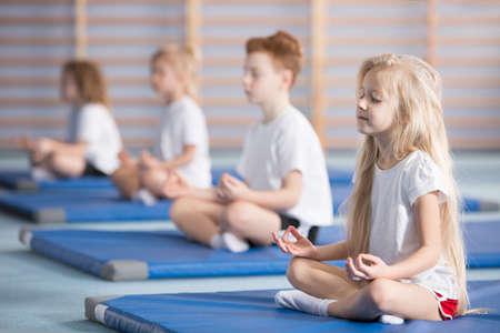 Grupa dzieci siedzi w pozycji lotosu na niebieskich matach podczas zajęć jogi