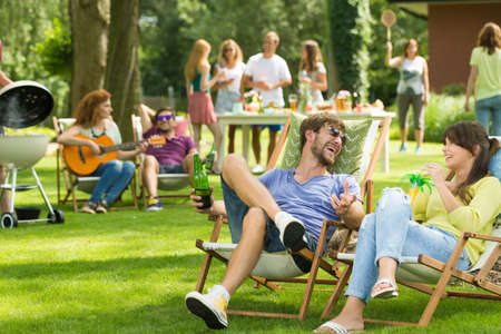 Friends sit on sunbeds and drink drinks while barbecuing in the garden with friends