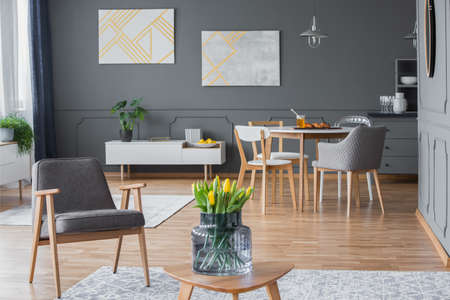 Yellow tulips and a modern gray armchair in a stylish, multifunctional living room interior with abstract paintings and designer dining chairs