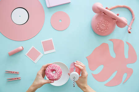Person eating pink doughnut and drinking a cocktail against blue background with leaf and phone 版權商用圖片