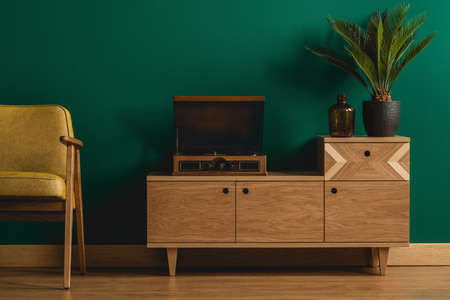 Close-up of a retro wooden dresser with a hipster record player in a minimalist dark green living room interior