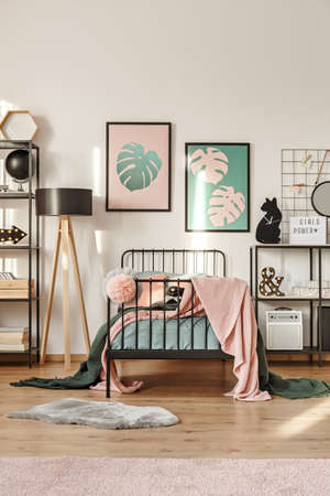 Two simple posters with Monstera Deliciosa leaves hanging above metal bed in girl room interior