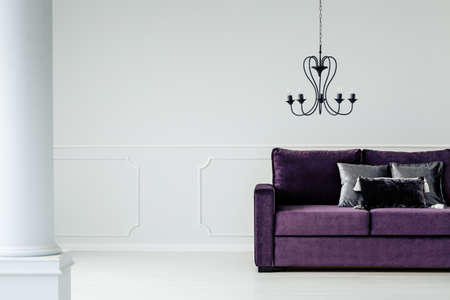 Lamp above purple couch with cushions in white glamour living room interior with copy space Imagens