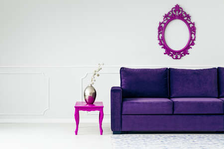 Silver vase on pink table next to violet sofa against white wall with frame in living room interior Stock Photo