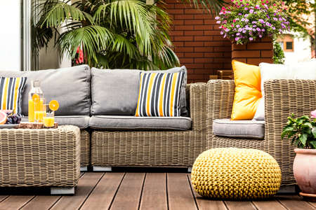 Yellow pouf next to a rattan armchair on wooden terrace with striped pillows on sofa