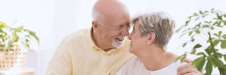 A close-up portrait of a happy senior couple - an older caucasian man and woman embracing face to face, touching noses and smiling in a white bright room with plants Foto de archivo