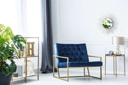 Navy blue chair standing in white room interior with golden furniture and decorations