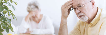 Close-up of a worried, elderly man deep in thoughts, with his hand on his forehead and a sad senior woman blurry in the background