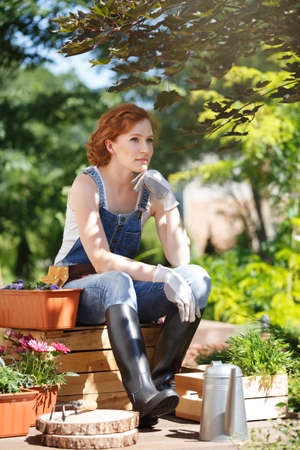 Young girl in wellingtons and dungarees, sitting on a palette and resting while working in the garden Stockfoto