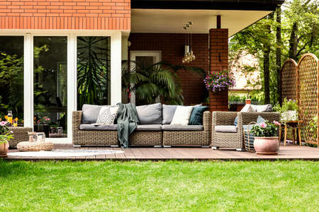 Grey pillows and blanket on garden furniture in front of a house in the summer