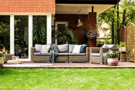 Oreillers gris et couverture sur mobilier de jardin devant une maison en été