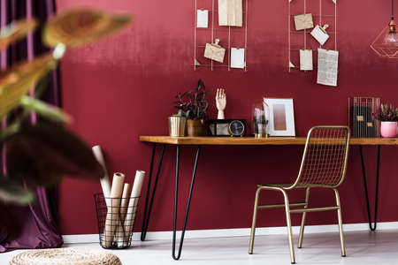 Gold chair at desk with clock and poster in cozy red workspace interior with cherry wall