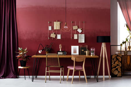 Burgundy cloth next to a table and wooden chair in elegant workspace interior with lamp