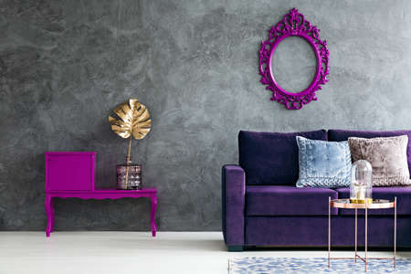 Gold leaf on purple cupboard in dark living room interior with violet sofa and mockup on concrete wall Imagens