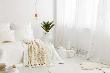 Bright, cozy bedroom interior with white bedding on the bed, palm plant and big window Foto de archivo - 99721247