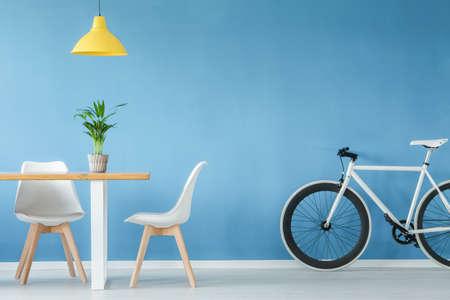 두 개의 의자가있는 최소한의 현대적인 인테리어, 자전거, 식물이있는 테이블 및 파란색 벽 위의 노란색 램프