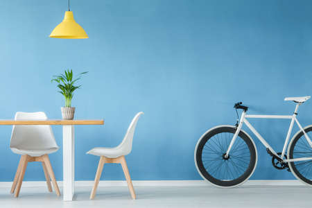 Minimal, modern interior with two chairs, a bicycle, a table with a plant on it and a yellow lamp above, against blue wall