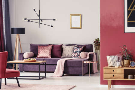 Maroon living room interior with ultra violet sofa, patterned pillows and golden frame on the wall Stok Fotoğraf