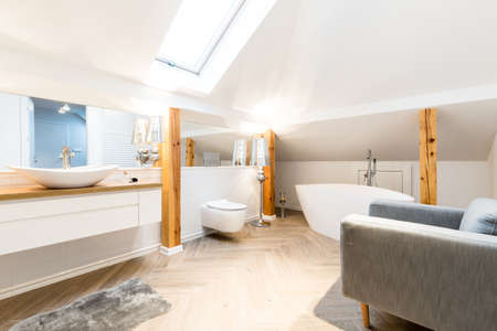 White, modern bathroom interior with armchair, roof window and oval sink