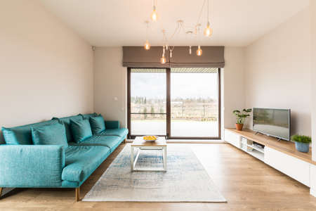 Luxurious living room interior with a turquoise sofa, big window and cabinet with a television o top